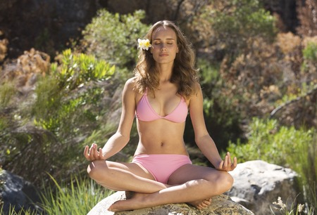 Young woman in a bikini practicing yoga Stock Photo