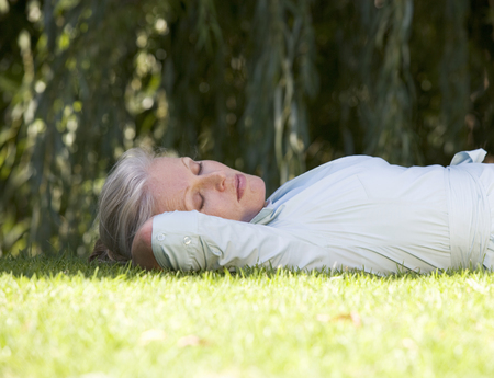 A senior woman asleep in the garden Stock fotó