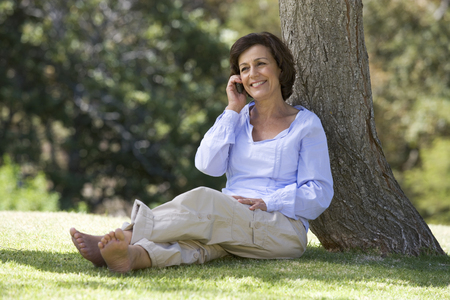 A senior woman sitting under a tree using a mobile telephone