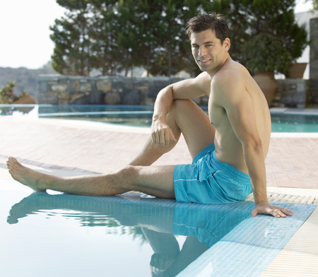 A man relaxing at the edge of a pool Stock Photo