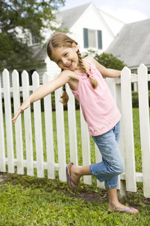 little girl posing standing by picket fence Stock Photo