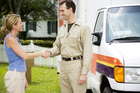 removals: Woman shaking hands with removal man beside his van