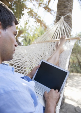 whilst: A man using a laptop whilst lying in a hammock