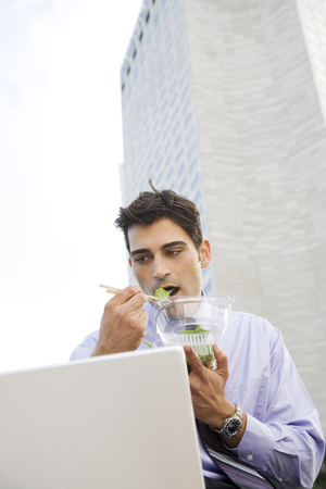 A businessman using a laptop and eating his lunch