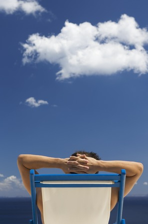 A man relaxing in a deck chair Banco de Imagens