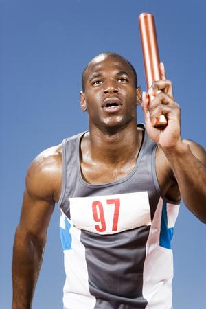 carrera de relevos: Relay runner with baton in his hand