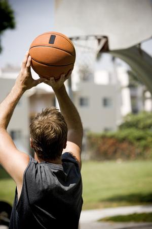 hombre disparando: aros hombre de disparo en una cancha de baloncesto urbano