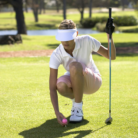 woman golf: Woman playing golf, teeing up LANG_EVOIMAGES