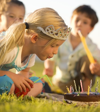 A young girl blowing out the candles on her birthday cake LANG_EVOIMAGES