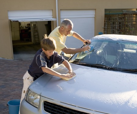 helps: Father and son washing a car