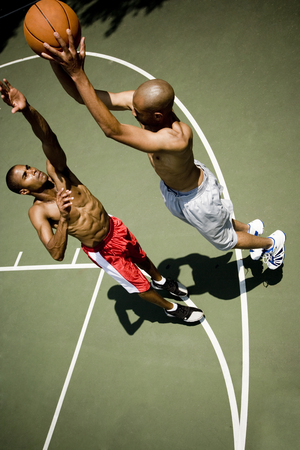 outdoor basketball court: Two men playing on an outdoor basketball court