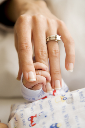 two people fertility: A mother holding her new babys hand