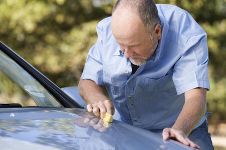 A senior man cleaning his car Stock fotó