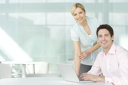 Two business colleagues at a laptop, smiling Stock Photo