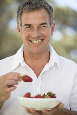 A man holding a bowl of strawberries