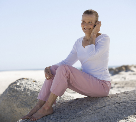 A mature woman sitting on a beach using a mobile phone