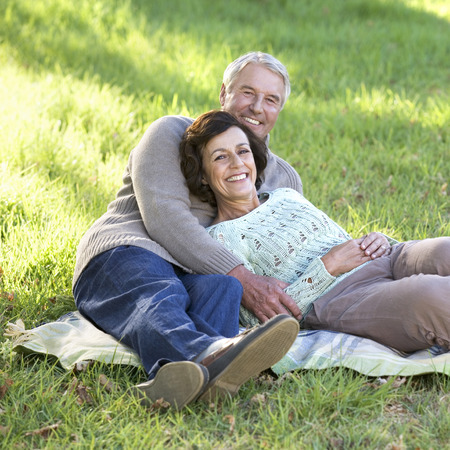 A senior couple laying on a rug