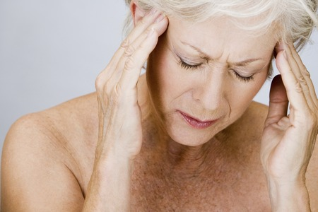 neuralgia: A senior woman with a headache, touching temples