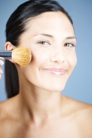 youthfulness: A young woman applying blusher with a brush LANG_EVOIMAGES