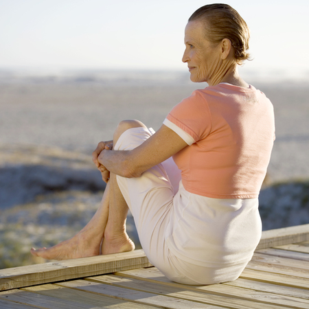 A mature woman sitting on a boardwalk LANG_EVOIMAGES