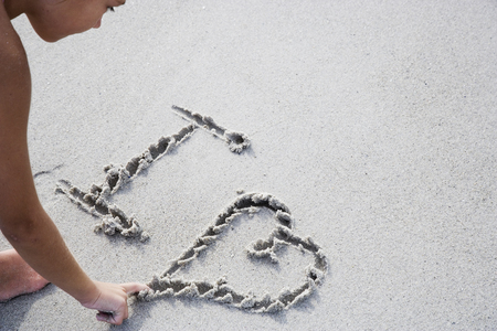 loveheart: A young girl writing in the sand