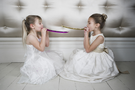 Two little girls wearing party dresses blowing party blowers LANG_EVOIMAGES