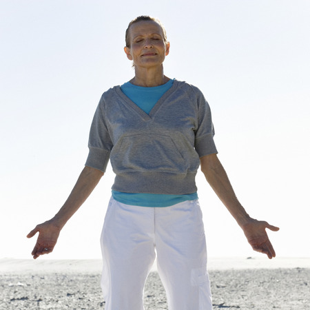 A mature woman meditating on a beach