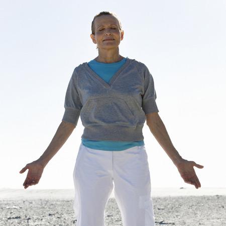 Una mujer madura meditando en una playa LANG_EVOIMAGES