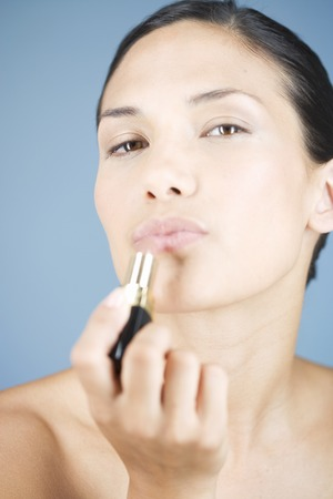 A young woman applying lipstick Stock Photo