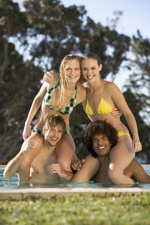 Four teenage friends having fun in a swimming pool