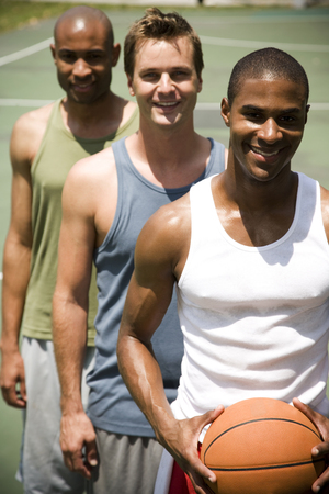 outdoor basketball court: Three men standing on an outdoor basketball court