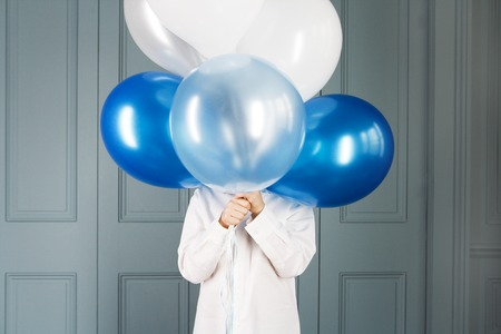 one child: boy hiding behind a bunch of balloons