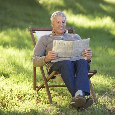A senior man sitting in a deck chair reading a newspaper