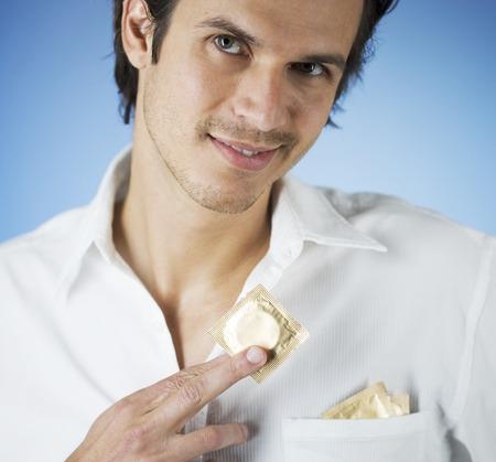 condones: Un hombre joven que poner condones en su bolsillo de la camisa