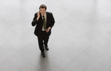 view of an atrium in a building: A businessman talking on mobile phone, smiling