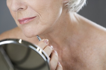 plucking: A senior woman plucking hairs from her chin with tweezers LANG_EVOIMAGES