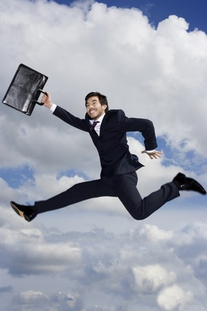 A businessman with briefcase, leaping in the air Stock Photo