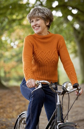 A senior woman riding a bicycle, smiling, Stock Photo