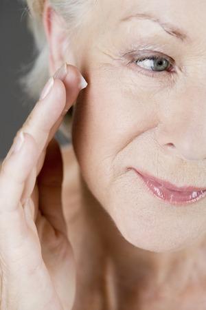 elasticity: Una mujer mayor que aplica la crema hidratante para la cara