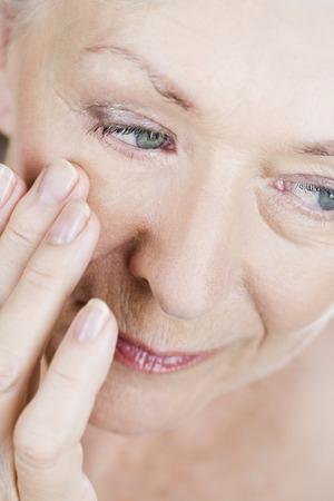 elasticity: A senior woman applying eye cream