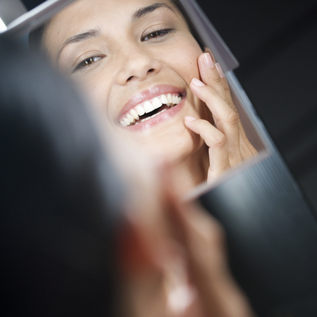 woman mirror: A young woman looking in a mirror