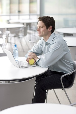 A man sitting at a laptop eating an apple Stock Photo