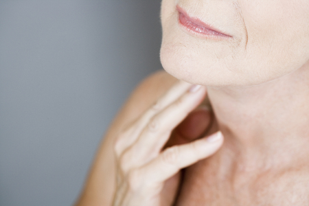 suppleness: A senior woman touching her neck