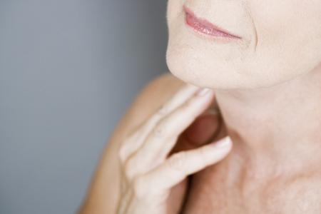 elasticity: Una mujer mayor que toca su cuello