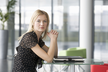 A businesswoman sitting in a modern office Stock Photo
