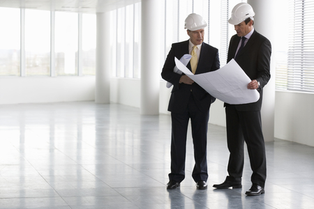 hard hats: Two architects wearing hard hats looking at plans