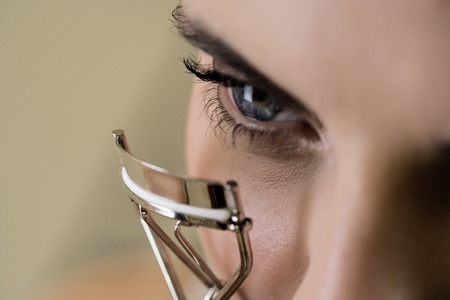 curling: Woman curling her eyelashes