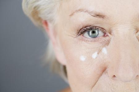 suppleness: A senior woman applying eye cream