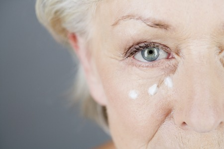 Una crema para los ojos mujer mayor de aplicar Foto de archivo - 64806981