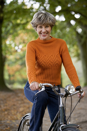 A portrait of a senior woman riding a bicycle, smiling,